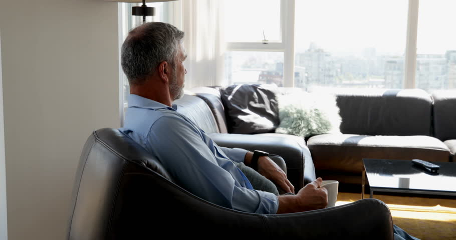 Senior Man checking time on smartwatch while having coffee on his couch at home | Shutterstock HD Video #1016460865
