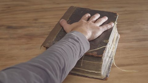 A man's palm on a old book, an oath on the bible. Top view from above