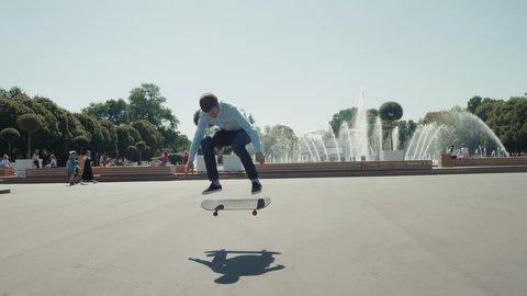 Close up of skater skateboarder man doing 360 kickflip heelflip flip trick in slow motion jump, ollie, city street park young professional man