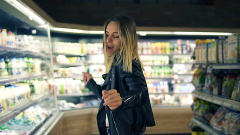 At the supermarket: happy young woman in black jacket dances through goods and dairy products on the shelves. Whirling, having fun, positive