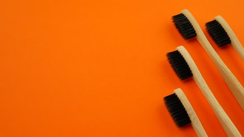 Black and rainbow bamboo toothbrushes on orange background. Concept of racism, social exclusion, depression or loneliness, social problems or illegal migration