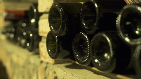 Wine bottles lying in stack at cellar. Glass bottles of wine stored in stone cellar in tavern. Interior underground wine cellar in restaurant