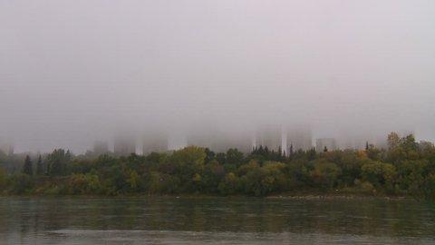 North Saskatchewan River flows past highrise buildings shrouded in fog. Edmonton, Canada.