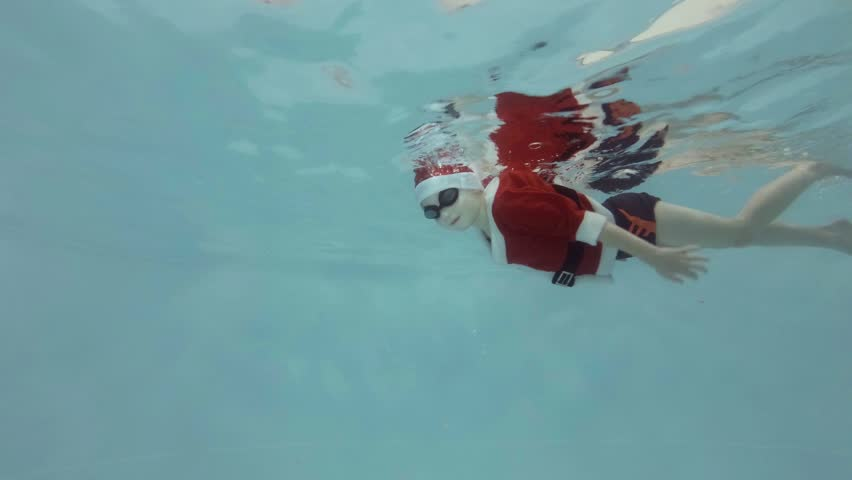 A little boy in a suit and hat Santa Claus swims underwater in the pool with glasses for swimming and looking at the camera. Slow motion. Side view. Raw video. Shooting underwater. 4K. 25 fps.