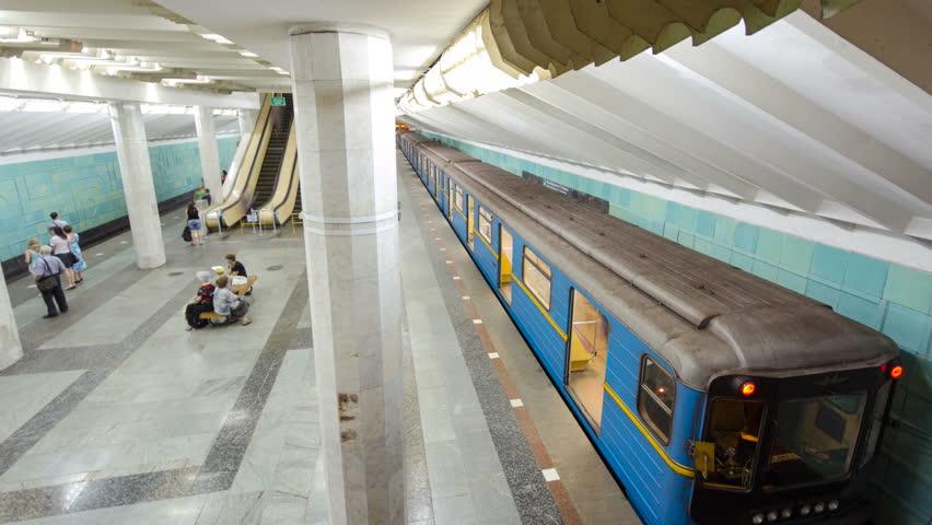 An underground train departing from Metrobudivnikiv metro station on Oleksievska Line of Kharkiv metro timelapse hyperlapse, with a passengers on a platform, in Kharkov, Ukraine