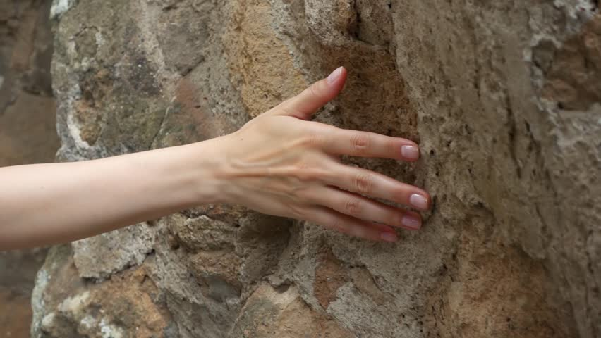 Woman sliding hand against old ancient stone wall in slow motion. Female hand touching hard rough surface of rock with green mold on it | Shutterstock HD Video #1016525035