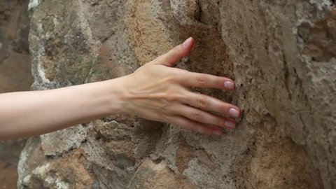 Woman sliding hand against old ancient stone wall in slow motion. Female hand touching hard rough surface of rock with green mold on it