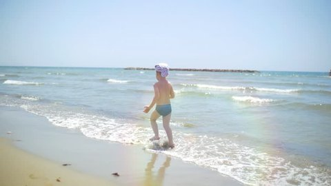 Child naked and barefoot running along the beach on a Sunny summer day. Happy boy resting on the sea, sunbathing and running in the water