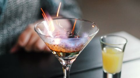 Bartender sets fire to cocktail, prepare alcohol beverage, barman makes drinks with fire next to the bar counter