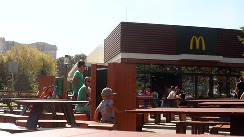 Lviv, Ukraine - September 19, 2018: time lapse view of young family people with child resting in outdoors cafe in sunny summer day mcdonalds company McDonald's Corporation business urban city