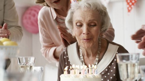 Beautiful senior woman  in party hat blowing off birthday candles on cake while joyous friends clapping hands and saying best wishes