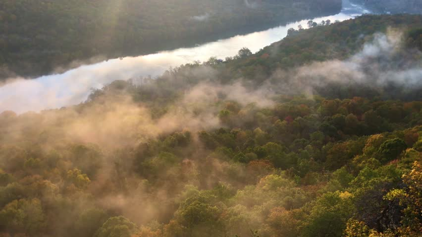 Fog over fall colors near river. | Shutterstock HD Video #1016612995