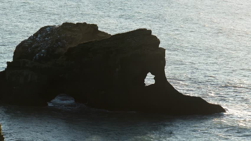 Aerial view of crashing waves breaking on strange looking black rock formation inside the sea