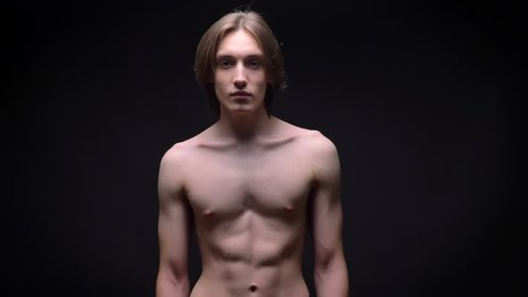muscular bare young white sportsman looking at the camera with power concentrated on black background