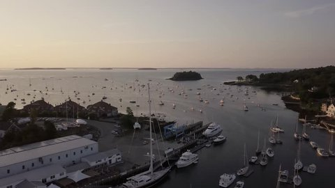 Aerial footage of an early morning flight over Camden harbor featuring many tall masted yachts and the Curtis Island lighthouse.