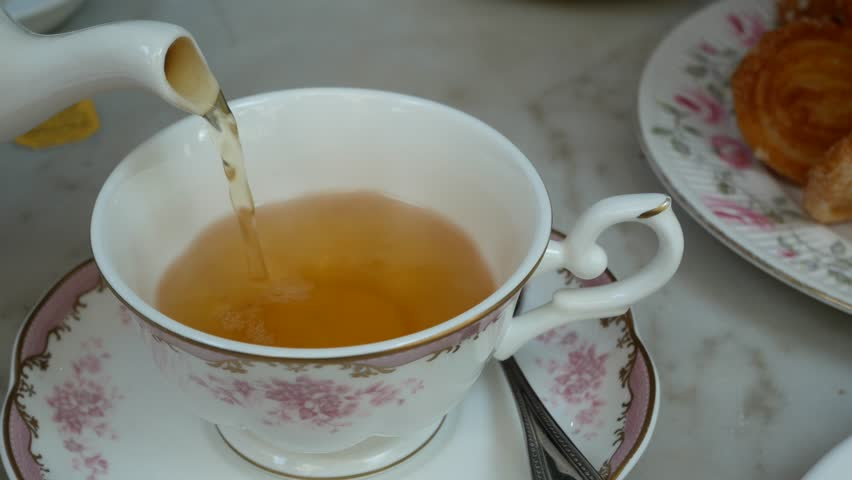 Pouring english tea into the beautiful english tea cup with background of sweet dessert (scone)