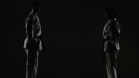 karate girl and boy having a fight, against dark background