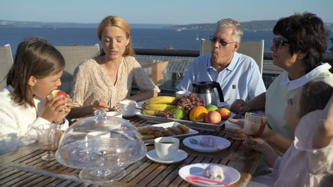 A big happy family has dinner on the open terrace on the roof of the house. Tea party on the summer terrace on the sea coast