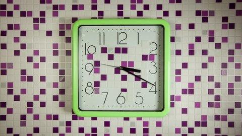 Time lapse clock - camera rotates with the big hand of a square kitchen clock from 04:00 to 05:00, before and after that the camera stops.