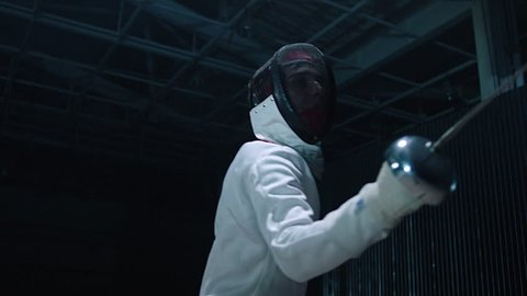Professional fencer in protective uniform practicing maneuvers with sword alone in dark studio . Fencing demonstration on black smoked background . Shot on Arri Alexa cinema camera in slow motion .