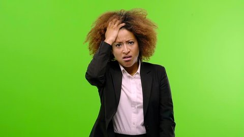 Young afro american businesswoman worried and overwhelmed, forgetful, realize something, expression of shock at having made a mistake