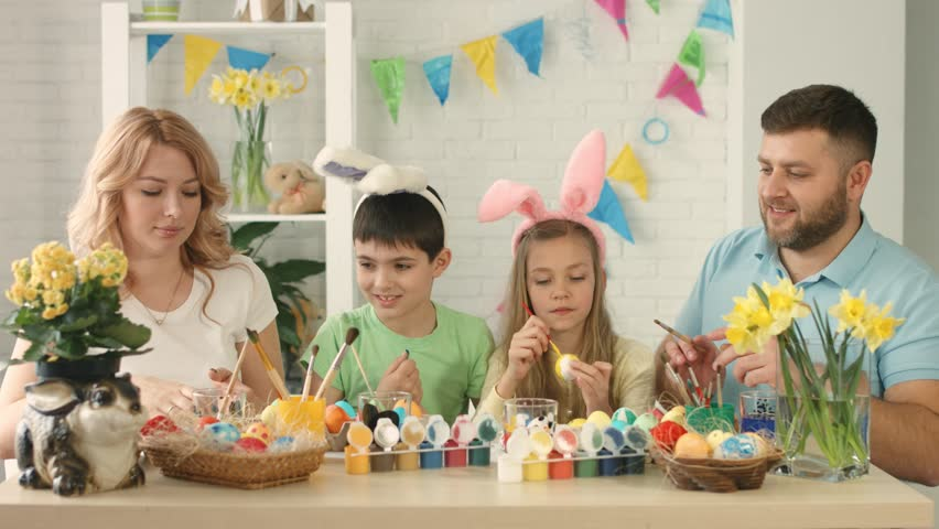 Portrait of a happy family with two children drawing Easter eggs | Shutterstock HD Video #1016797885
