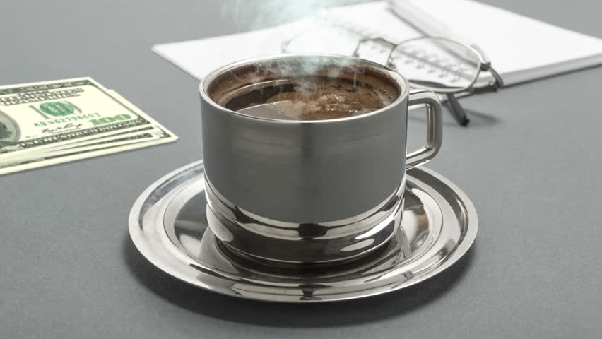 CINEMAGRAPH - Still life photo with cup of coffee, book, pen, money, and glasses on gray background.  | Shutterstock HD Video #1016822635