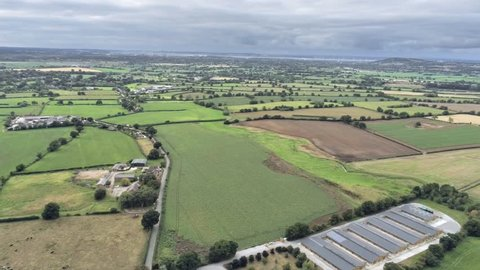 Aerial view, semi panorama panning move. Sewage works, houses among fields on Cheshire countryside. Tarvin in background