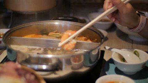 Enjoying a prawn from a Sukiyaki soup at Home. Slow Motion.