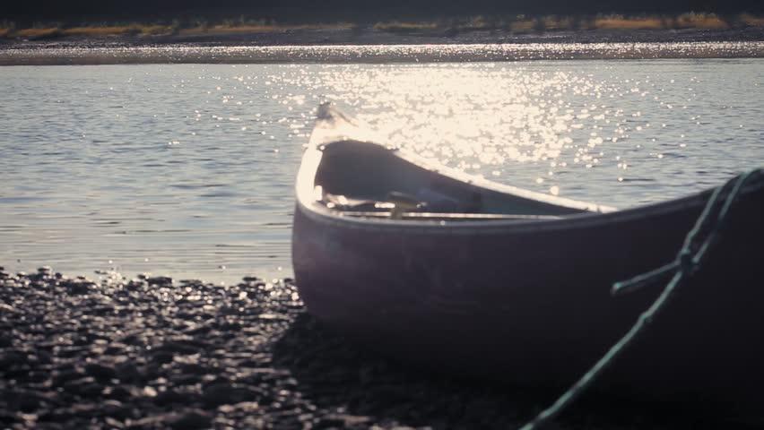 Yukon River, Yukon Territories, Alaska. Metalic canoe on a pebble beach in the sunset. Yukon River.