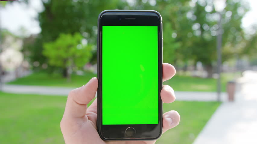 New York, USA - July 2018: A hand holding a phone with a green screen in a public park. Close-up shot. Soft focus | Shutterstock HD Video #1016879275