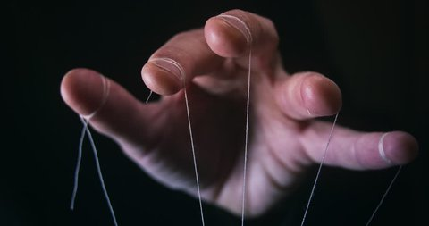 Closeup of a Puppet Master hand with string