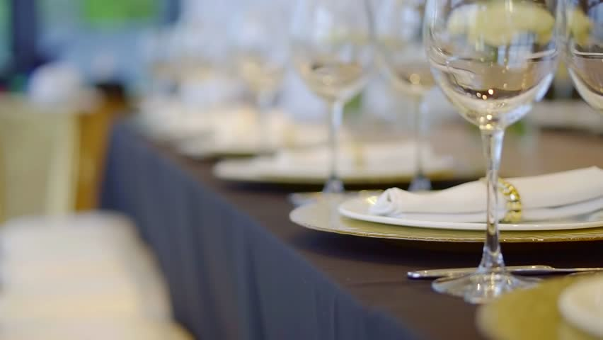 waitress is putting forks on a table for gala dinner in restaurant, close-up of her hands