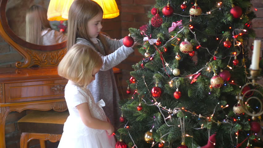 Children decorate the Christmas tree in the room, prepare for the holiday | Shutterstock HD Video #1016898265