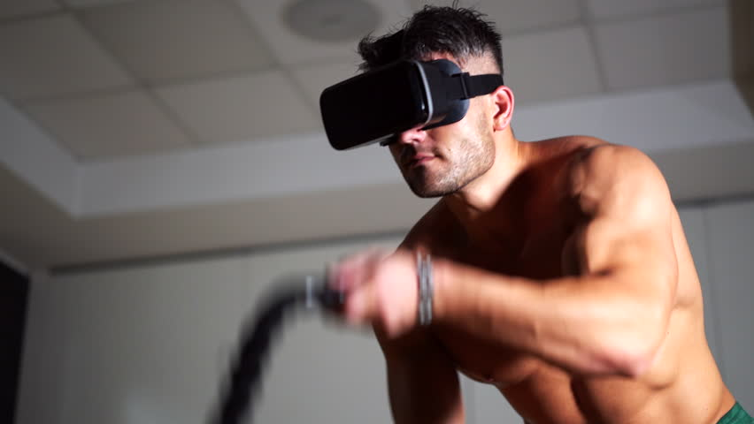 Virtual reality technology in sport. Man working out with battle ropes in the gym. Cross fitness workout. VR glasses concept. 4K UHD. | Shutterstock HD Video #1016902375