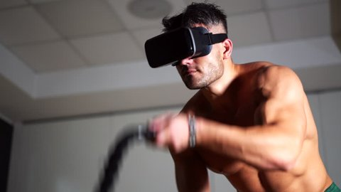Virtual reality technology in sport. Man working out with battle ropes in the gym. Cross fitness workout. VR glasses concept. 4K UHD.