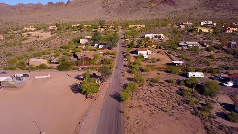 Aerial shot flying over houses panning up to see the north end of the Superstition Mountains in Apache Junction Arizona.