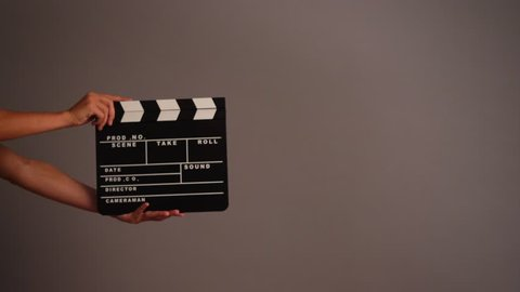 Movie clapper against grey background.