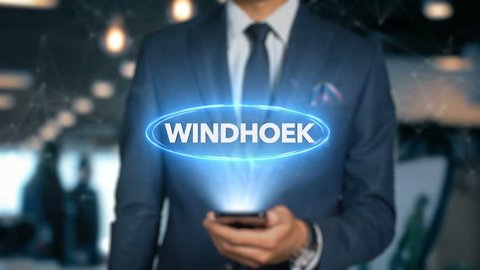 Businessman With Mobile Phone Opens Hologram HUD Interface and Touches Word Country - Capital - WINDHOEK