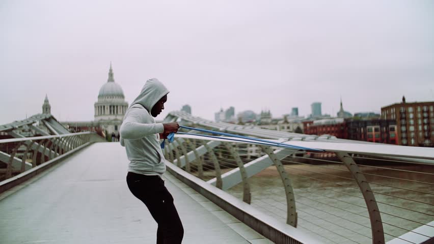 Young active black sportsman exercising with elastic rubber bands in London. | Shutterstock HD Video #1016953525