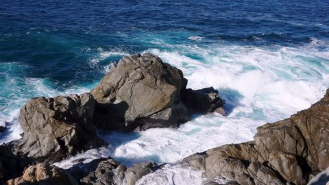 Gentle but powerful waves of the Pacific Ocean washing against rocks on the cost of Big Sur, California. Shot looking down from a high vantage point.