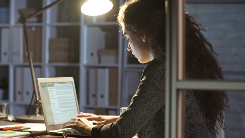 Young female journalist writing an article on laptop while working alone in office at night | Shutterstock HD Video #1016969965