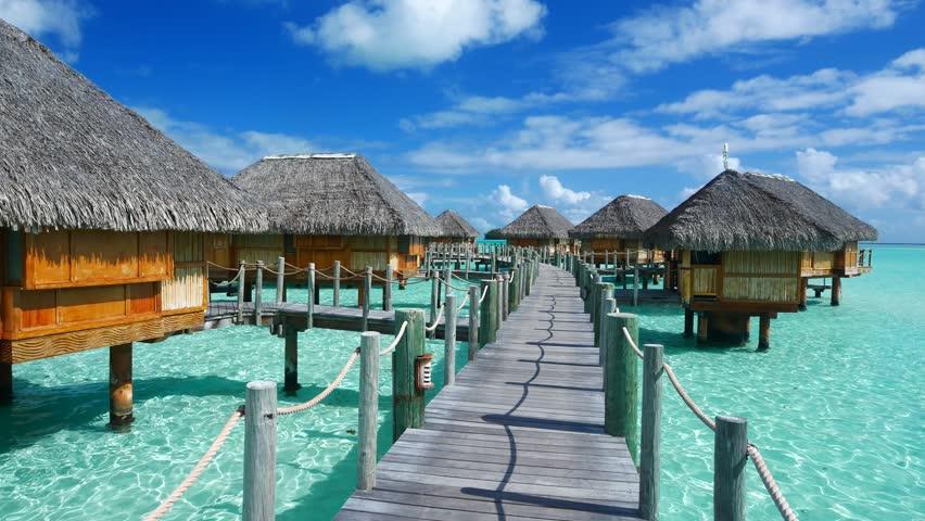 Luxury overwater villas on blue lagoon, white sandy beach and Otemanu mountain at Bora Bora island, Tahiti, French Polynesia