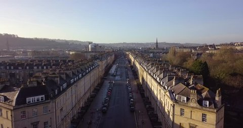 Aerial footage in City of Bath, of a street in bath with Georgian architecture buildings on either side,ing toward centre of Bath