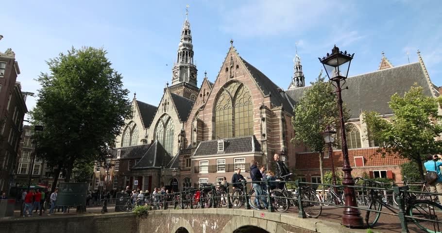 Amsterdam, Netherlands - September 2018: Peoples walking on the bridge near the Oude Kerk or Old Church