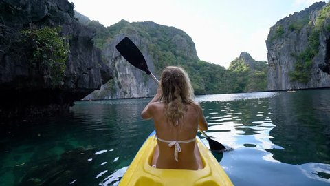 Woman exploring calm tropical bay with limestone mountains by kayak in the Philippines. People travel destinations tropical beaches concept ; People discovery adventure in holidays