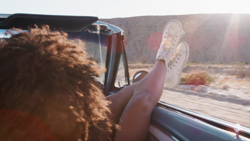 Young woman with legs sticking out of moving car, back view | Shutterstock HD Video #1017037795