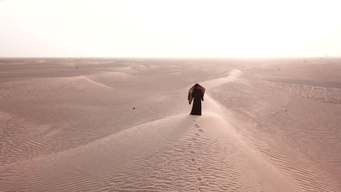 A single woman in abaya (United Arab Emirates traditional dress) walking on the dunes in the desert towards the sunrise bring light. Dubai, UAE.
