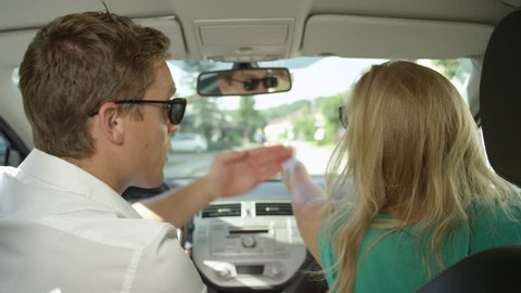 CLOSE UP: Young couple argues while driving through the sunny suburban area. Caucasian girlfriend and boyfriend screaming and fighting during their summer road trip. Tourists quarreling in the car.