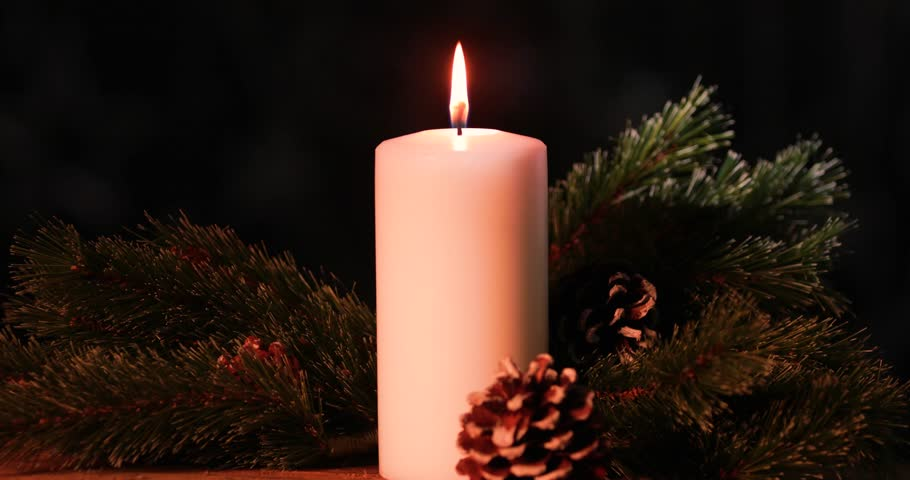 Burning Christmas candle with pine cones and fir tree on dark background. Shot in 4k resolution | Shutterstock HD Video #1017064075